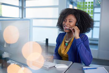 Customer service representative talking to a client on a headset