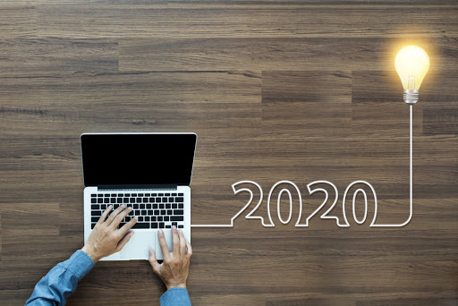 "Stock image of a person's hands typing on a laptop, with ""2020"" written as a cord coming from the laptop and ending in a lit lightbulb."