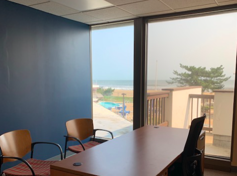 Three empty chairs around a desk in an office with a large window, where the view overlooks a beach.